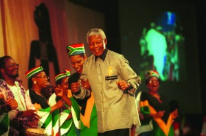 """Nelson Mandela is greeted at the 8th assembly of the World Council of Churches in Harare, Zimbabwe, in December 1998. """"Journey to Jubilee"""": South African Choir Photo by Chris Black/WCC."""