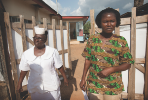 Mbalu Fonnie, head nurse in the hemorrhagic fever ward, and nurse Veronica Karoma describe efforts to contain the Ebola virus outside the gates to the isolation ward at the government hospital in Kenema, Sierra Leone. Photo by Mike DuBose, UMNS.