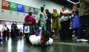 Protestors lie on the floor of the 2016 General Conference, their hands and feet bound to protest the denomination's policies on human sexuality. Photo by Paul Jeffrey, UMNS.