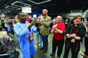 An African visitor uses his mobile phone to record LGBTQ protestors on the floor of the 2016 United Methodist General Conference in Portland. Photo by Paul Jeffrey, UMNS.