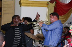 The Rev. Guillermo Leon Mighthy holds the microphone for trumpet player Jorge Lázaro Corrales Estradas. Photo by Steve Beard.